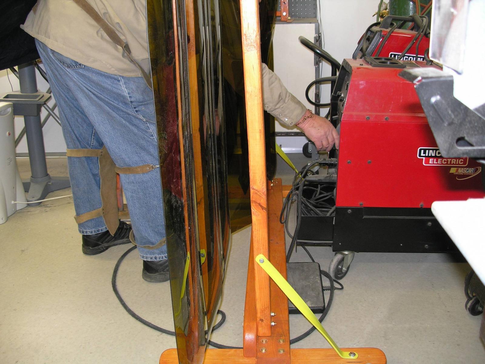 Reaching through screen to make an adjustment on welder